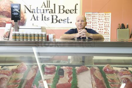 Bald : Supermarket employee stands at meat counter in supermarket