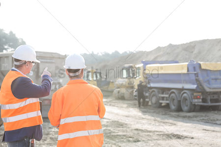Supervisor : Supervisor explaining plan to colleague at construction site