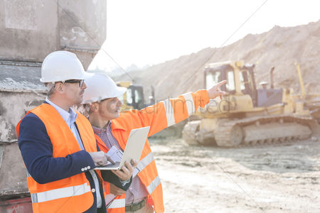 Supervisor : Supervisor showing something to coworker holding laptop at construction site