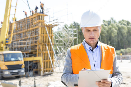 Supervisor : Supervisor writing on clipboard at construction site