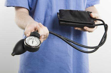 Examination : Surgeon with blood pressure gauge mid section