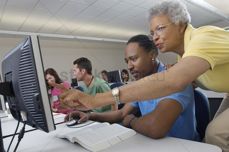 College : Teacher helping student in computer class