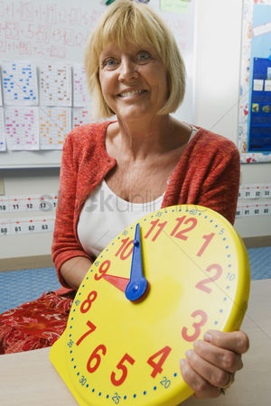 Instruction : Teacher holding a time teaching clock