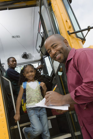 Schoolkids : Teacher unloading elementary students from school bus