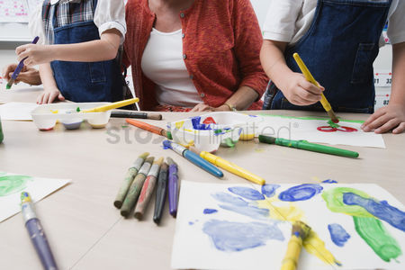 School children : Teacher watching students paint