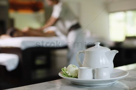 Spa : Teapot and tea cups  woman receiving massage on the background