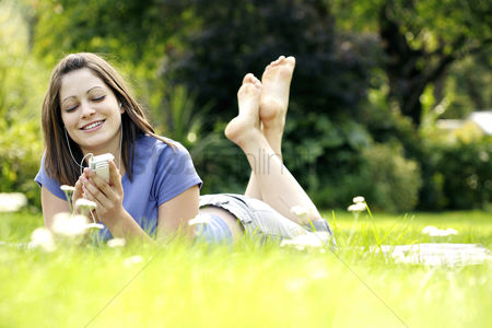 Enjoying : Teenage girl lying forward on the field listening to music on a portable mp3 player