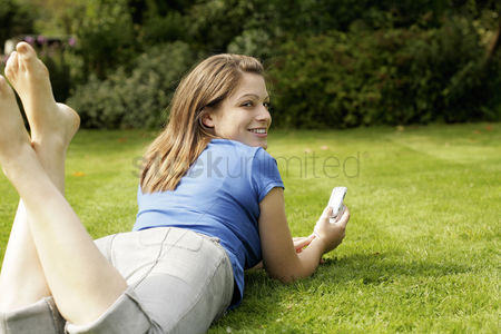 Lying forward : Teenage girl lying forward on the field playing with her mobile phone