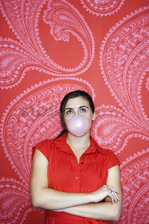 Blowing : Teenaged girl blowing bubble against pink and red patterned wallpaper