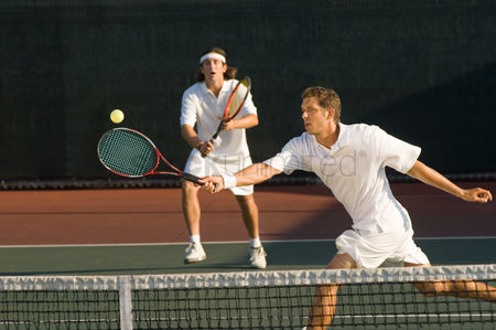 Match : Tennis player stretching swinging at ball near tennis net doubles partner standing behind
