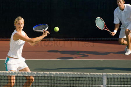 Match : Tennis player swinging at ball near tennis net  doubles partner squatting behind