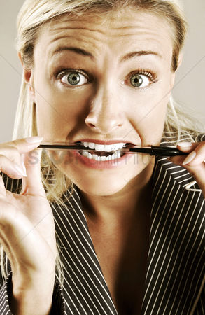 Attitude : Tensed up woman biting a pen