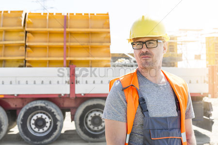 Supervisor : Thoughtful architect standing against truck at construction site