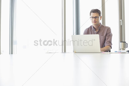 Internet : Thoughtful businessman looking away while using laptop at desk in creative office