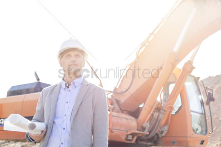 Supervisor : Thoughtful engineer looking away while holding blueprints by bulldozer at construction site