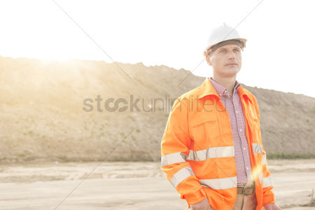Supervisor : Thoughtful male supervisor looking away at construction site