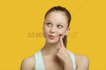 20 24 years : Thoughtful young woman looking sideways over yellow background