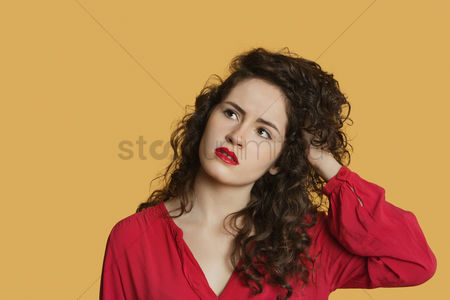 Contemplation : Thoughtful young woman with hand in hair over colored background