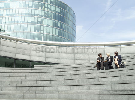 Steps : Three business people sitting on stairs outdoors talking