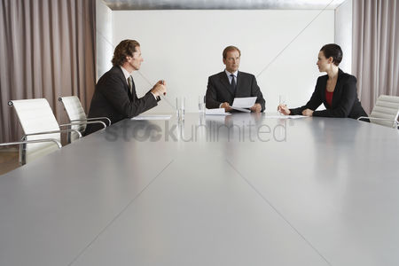 Spacious : Three businesspeople meeting in conference room
