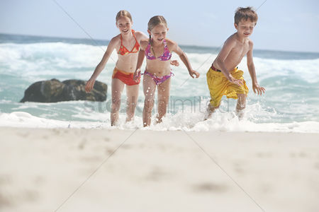 Appearance : Three children  5-6 7-9 10-12  running on beach