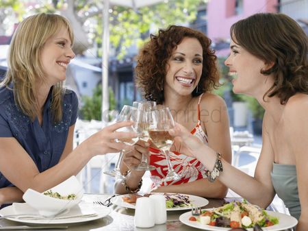 Appearance : Three female friends toasting drinks at outdoor cafe