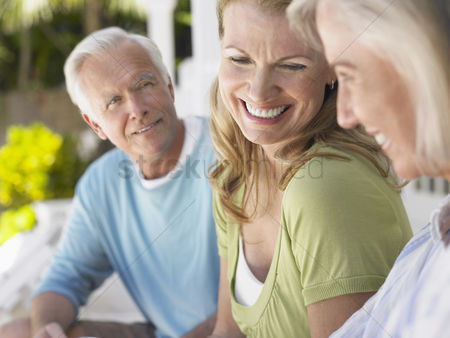 Mature : Three people sitting on verandah