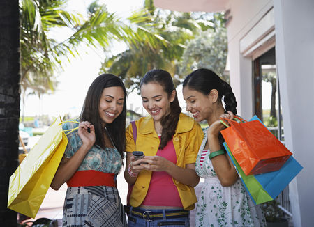 Shopping : Three teenage girls  16-17  on street holding shopping bags and text messaging
