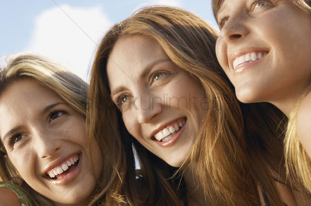 Friends : Three young women sitting side by side looking at view close up head and shoulders