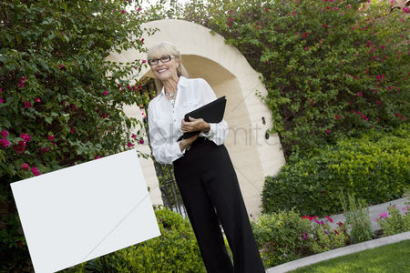 Senior women : Tilt shot of cheerful senior agent standing by sign board with clipboard