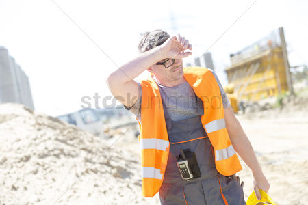 Supervisor : Tired construction worker wiping forehead at site