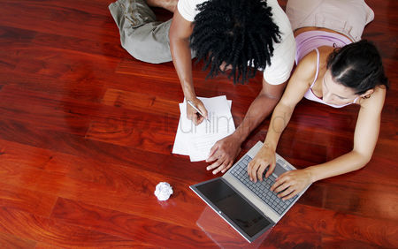 Friends : Top view of an african american guy and a lady sharing a laptop on the floor