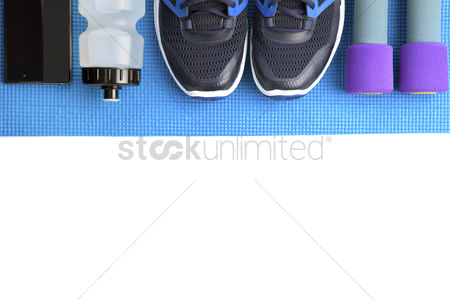Background : Top view of fitness equipment on white background with copyspace