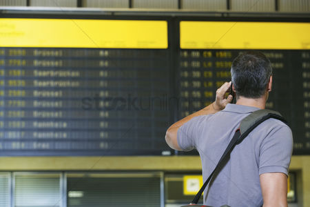 Cell phone : Traveller using mobile phone in front of flight status board in airport