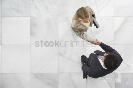 People : Two business people shaking hands in lobby