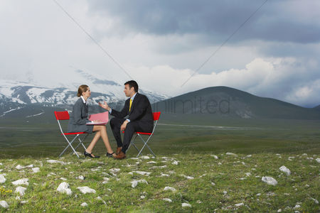 Moody : Two business people sitting and talking in mountain field side view