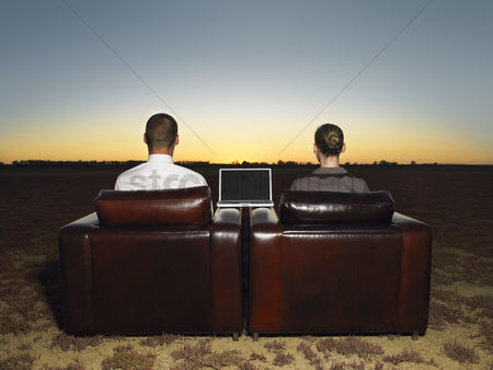 Land : Two business people sitting in armchairs in open plain at sunset back view