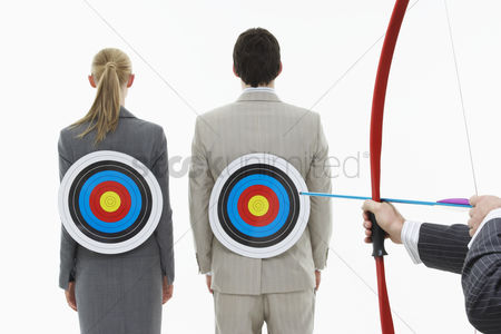 Toy : Two business people with targets on backs while man aims bow and arrow  close-up of hands  against white background