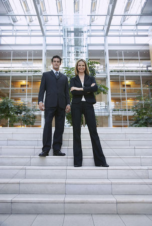 Proud : Two businesspeople standing outside office portrait