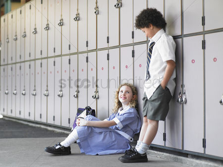 Pocket : Two elementary school students waiting by school lockers
