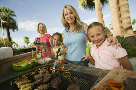 Posed : Two girls  7-9  with family at outdoor barbecue portrait