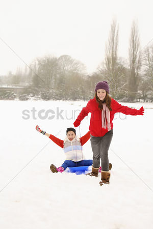Cold temperature : Two girls playing in the snow  riding sled