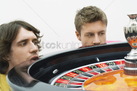 Worry : Two hopeful  young men crouching at roulette wheel watching spin close up