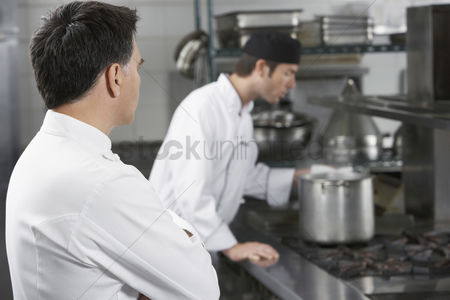 Supervisor : Two male chefs working in kitchen