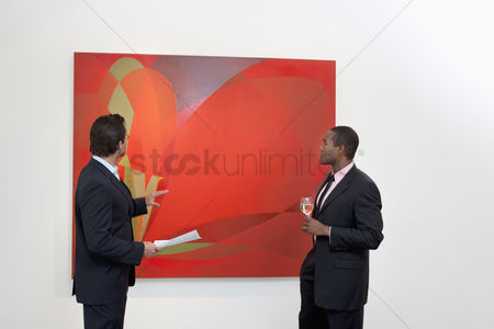 Interior background : Two males talking over painting in art gallery