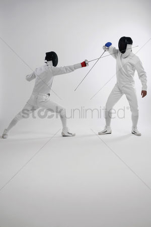 Fight : Two men in fencing suits dueling