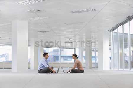 Interior : Two office workers sitting face to face using laptops on floor of empty office space