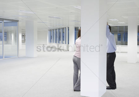 Spacious : Two office workers talking behind column in empty office space