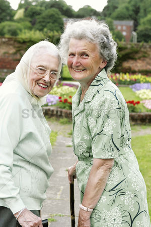 Friends : Two old women with walking sticks walking in the park
