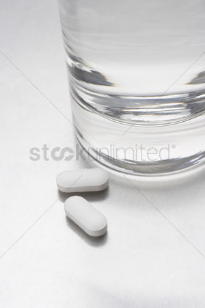 Medication : Two pills beside glass of water